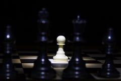 Weißes Pfand, das allein im Scheinwerfer auf Schachbrett mit Schwarzem steht Lizenzfreie Stockfotos