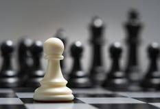 Weißes Pfand vor dem hintergrund der dunklen Schachfiguren Lizenzfreie Stockfotos