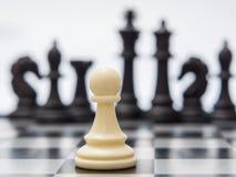 Weißes Pfand vor dem hintergrund der dunklen Schachfiguren Stockbild