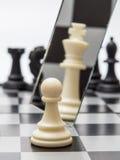 Weißes Pfand vor dem hintergrund der dunklen Schachfiguren Lizenzfreies Stockfoto