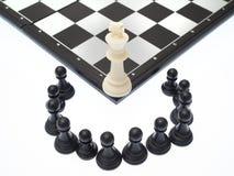 Weißes Pfand vor dem hintergrund der dunklen Schachfiguren Lizenzfreie Stockbilder