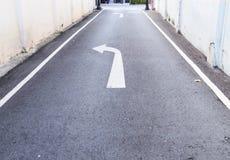 Weißes PfeilVerkehrszeichen zeigt Nebenstraße an, um zur Hauptstraße und zu den weißen Fußwegenlinien auf der Asphaltlandstraße h stockbild