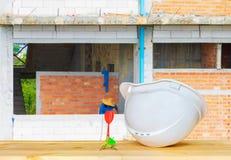 Weißes Plastiknachlässiges des Sturzhelms mit dem Hut-Schutzausrüstungsarbeiten mit drei Pfeilen des Technikkonzeptes auf Holz stockfoto