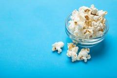 Weißes Popcorn auf einem blauen Hintergrund Kopieren Sie Platz stockfotografie