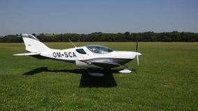 Weißes propellergetriebenes Flugzeug Kreuzers PS-28 DoppelSeats entfernt sich auf Graslandebahn in Co stock video