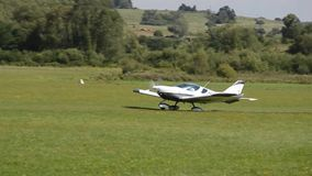 Weißes propellergetriebenes Flugzeug Kreuzers PS-28 DoppelSeats entfernt sich auf Graslandebahn in Co stock video footage