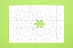 Weißes Puzzle auf grünem Hintergrund Stockbilder