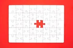 Weißes Puzzle auf rotem Hintergrund Lizenzfreie Stockfotos