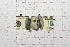 Weißes Puzzlespiel auf hundert Dollar Banknoten lizenzfreie stockfotos