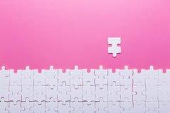 Weißes Puzzlespiel auf rosa Hintergrund Beschneidungspfad eingeschlossen stockbild