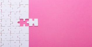 Weißes Puzzlespiel auf rosa Hintergrund Fehlendes Stück stockbilder