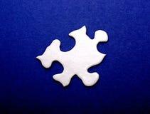 Weißes Puzzlespiel-Stück auf Blau Stockfotos