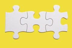 Weißes Puzzlespielstück auf gelbem Hintergrund Stockfotografie
