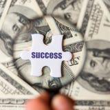 Weißes Puzzlespielstück mit dem Aufschrift Erfolg und Lupe auf einem Dollarscheinhintergrund lizenzfreies stockbild