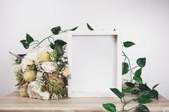 Weißes Rahmenmodell mit Blume und Rebe Stockfotos