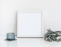 Weißes Rahmenmodell mit brunia und Kerze Lizenzfreie Stockfotos