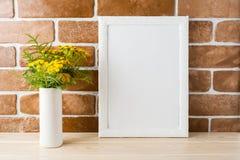 Weißes Rahmenmodell mit nahen herausgestellten Backsteinmauern der gelben Blumen Lizenzfreies Stockbild