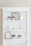 Weißes Regal mit Weinleseporzellangeschirr im Haus Stockbild