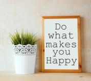 Weißes Reißbreit mit der Phrase tun, was macht Sie glückliches geschrieben auf es gegen strukturierte Wand ist Stockbilder