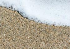 Weißes Seeschaumgummi auf Körnern eines des gelben Brauns Sandes stockfoto
