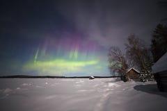 Weißes Seeufer unter den Lichtern des aurora borealis Stockfotografie