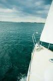 Weißes Segelboot über einem grünen See Lizenzfreie Stockbilder
