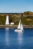 Weißes Segelboot, das einen weißen Leuchtturm im blauen Wasser führt Lizenzfreie Stockbilder