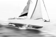 Weißes Segelboot, das Geschwindigkeit während des Anfangs nimmt Stockfotos