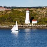Weißes Segelboot und Leuchtturm Stockbild