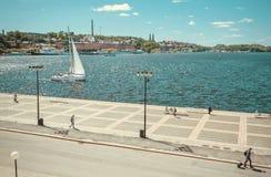 Weißes Segelbootsegeln auf den Wellen weg vom Riverbank in der alten Stadt mit entspannenden Leuten Lizenzfreie Stockbilder