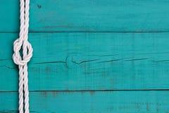 Weißes Seil mit Knotengrenze auf antikem Knickentenblauzeichen Lizenzfreies Stockbild