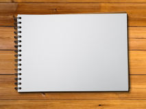 Weißes Skizzebuch auf Holz Stockfotografie