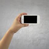 Weißes Smartphone in der Frauenhand auf Zementwandhintergrund Lizenzfreies Stockbild
