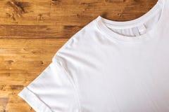 Weißes T-Shirt auf einem hölzernen Hintergrund lizenzfreie stockfotografie