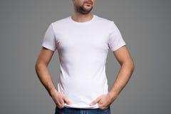 Weißes T-Shirt auf einer Schablone des jungen Mannes Grauer Hintergrund lizenzfreie stockbilder