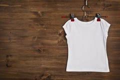 Weißes T-Shirt, das am hölzernen Hintergrund hängt Lizenzfreie Stockfotografie