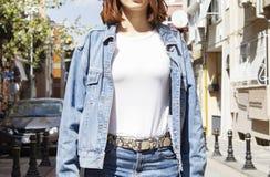 Weißes T-Shirt und Denim des Schablonen- und Modellfreien raumes, die gegen graue Straßenwand, für Druckspeicher aufwirft stockfotografie