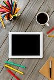 Weißes Tablet mit leerem Bildschirm auf dem hölzernen Desktop Stockfotos