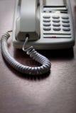 Weißes Telefon auf hölzernem Schreibtisch Stockfotografie