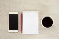 Wei?es Telefon mit einer Tasse Kaffee-, Notizblock- und Stiftl?ge auf einem wei?en Holztisch stockfotos
