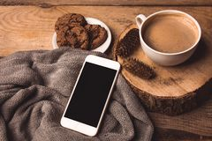 Weißes Telefon, Tasse Kaffee, Plätzchen und Kegel auf dem Tisch stockfoto
