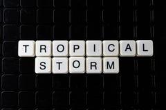 Weißes Textwort des tropischen Sturms auf schwarzer Abdeckung Textwortkreuzworträtsel Alphabetbuchstabe blockiert Spielbeschaffen Lizenzfreies Stockbild