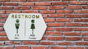 Weißes Toilettenzeichen auf bricked Wand Stockfotografie