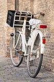 Weißes Transportfahrrad mit Kiste parkte gegen Backsteinmauer, Amsterdam, die Niederlande Stockbilder