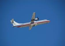 Weißes Triebwerkflugzeug, das gegen blauen Himmel sich entfernt Lizenzfreies Stockbild