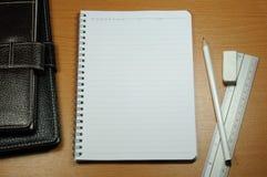 Weißes unbelegtes Notizbuch auf hölzerner Tabelle Lizenzfreie Stockbilder