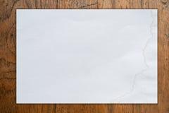 Weißes unbelegtes Papier auf hölzernem Hintergrund Stockfotografie