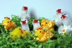 Weißes und gelbes Plüschostern-Huhn erscheint im grünen Nest Stockfotos