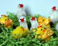 Weißes und gelbes Plüschostern-Huhn erscheint im grünen Nest Lizenzfreies Stockfoto
