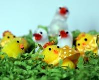 Weißes und gelbes Plüschostern-Huhn erscheint im grünen Nest Lizenzfreie Stockfotografie